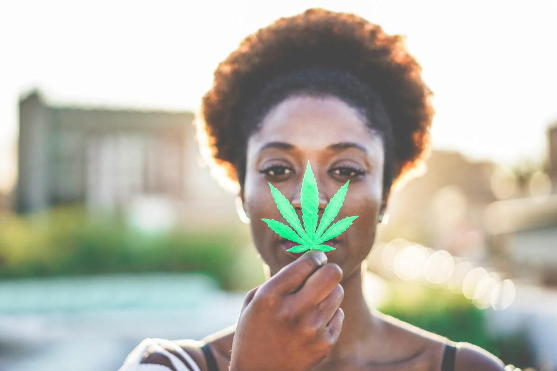 A woman holding a CBD cannabis leaf.